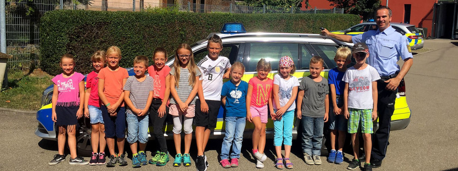 Gruppenbild vor dem Polizeiauto beim Sommerferienprogramm
