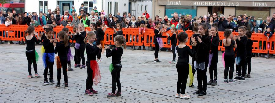 Kinder tanzen auf dem Marktplatz