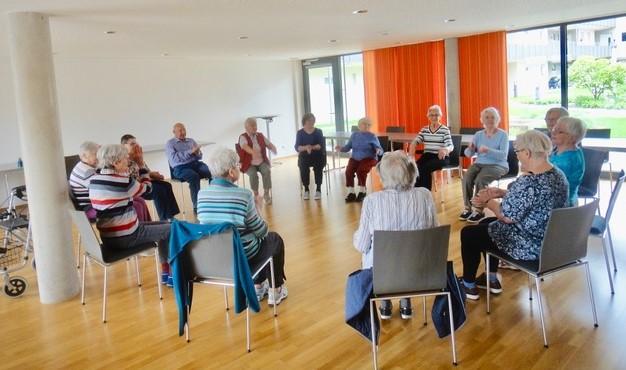 Eine Gruppe von Senioren sitzt in einem Stuhlkreis und betreibt Sitzgymnastik.