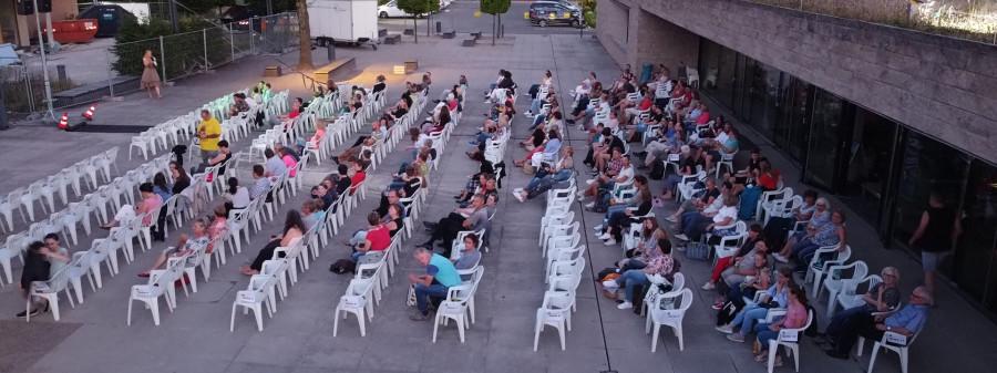 Zuschauer, die auf weißen Plastikstühlen mit Blick auf die Leinwand n Reihen sitzen.